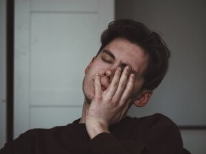 Man experiencing symptoms of digital eye strain rests while holding face in hands