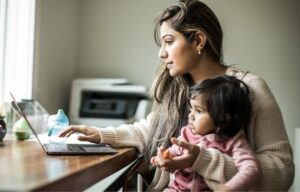 Woman on laptop with child on her lap