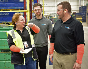 Three people talking on the shop floor in an industrial environment
