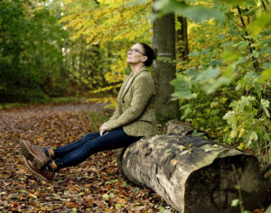 Woman sitting on a tree trunk looking at fall leaves