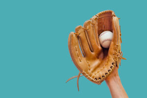 Hand In A Leather Baseball Glove Catches A Baseball on a Blue Background