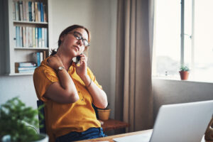 Woman experiencing neck pain while working from home